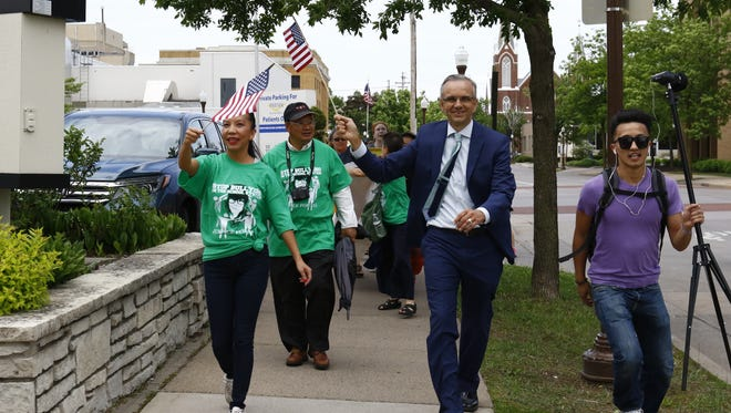 Hundreds of demonstrators, including Marathon County Administrator Brad Karger (in suit), rally May 31 in a peace march inspired by the guilty verdict against 16-year-old Dylan Yang, who was convicted of homicide in March. Marchers walked past the Wausau Police Department, the Wausau School District's administration building and the Marathon County Courthouse.