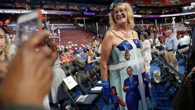Mississippi delegate Kelly Jacobs poses for picture as she shows off her dress with print showing a picture of President Barack Obama and First Lady Michelle Obama before the start of the third day session of the Democratic National Convention in Philadelphia, Wednesday, July 27, 2016.