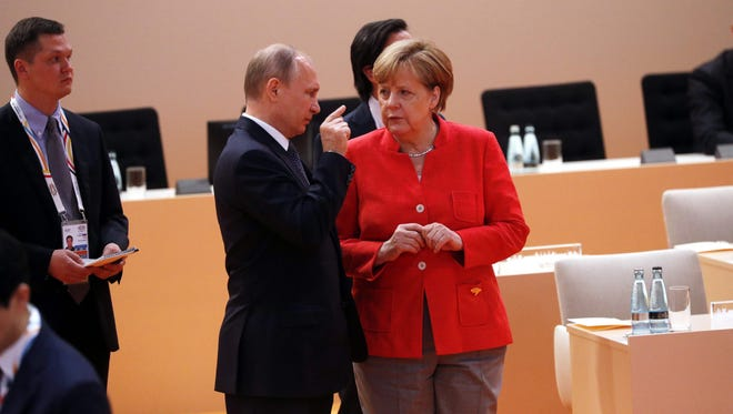 German Chancellor Angela Merkel talks to Russia's President Vladimir Putin  at the start of the first working session of the G20 meeting in Hamburg, northern Germany, on July 7.