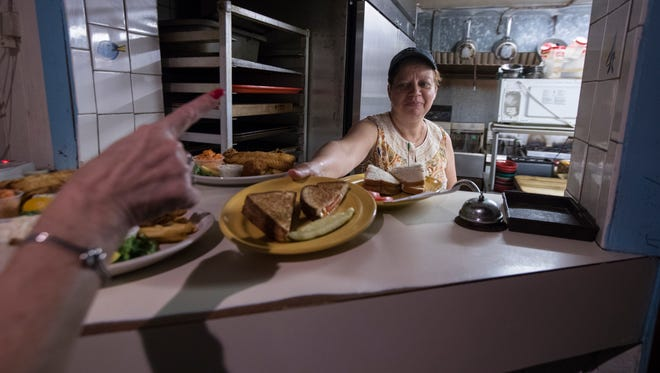 Jenny Domaso, a cook at Thirsty's Restaurant in Cape Coral, sends out lunch orders for her customers Friday, July 21. Domaso has been a cook at the restaurant  for 27 years.