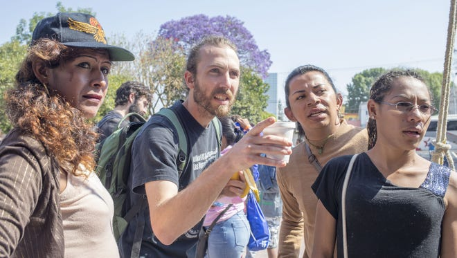 Alex Mensing, an organizer with the advocacy group Pueblo Sin Fronteras, talks to transgender migrants from Central America outside a church in Puebla, Mexico.