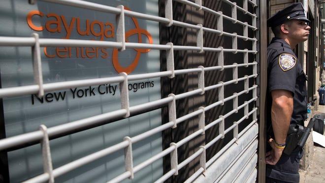 Un oficial de policía custodia las instalaciones del Centro Cayuga en N.Y., el cual alberga niños migrantes.