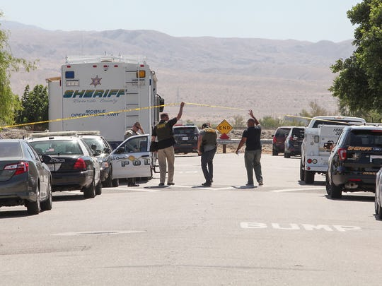 Police enter the taped-off scene at Calle Mendoza and Las Flores Avenue in Coachella, May 26, 2017. A Riverside County sheriff's deputy was shot at the intersection and a suspect was at large.