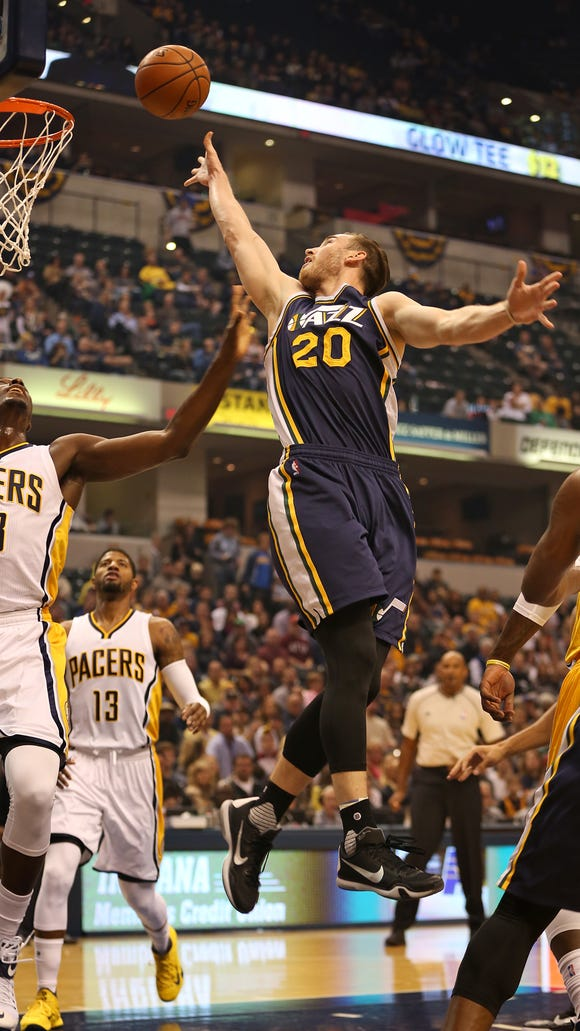 Utah's (and formerly Butler's)  Gordon Hayward shot over Pacers' #28 Ian Mahinmi and #13 Paul George during the Utah Jazz at Indiana Pacers game, Saturday,