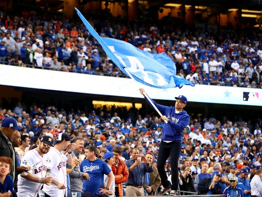 Actor Rob Lowe waves a Los Angeles Dodgers flag before