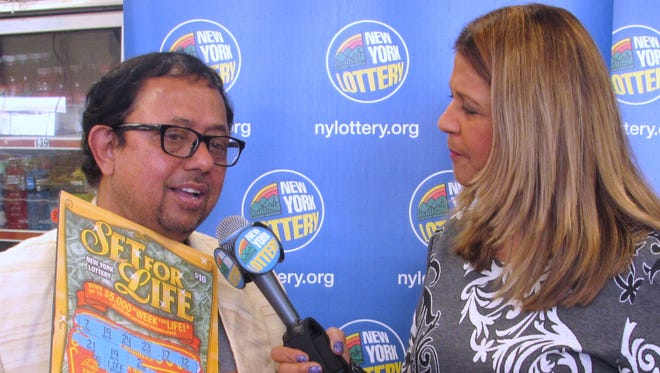 Lekhnath Ghimire, of Painted Post, explains to New York Lottery spokeswoman Yolanda Vega on Thursday how he reacted when he realized he won $5 million in the lottery's Set for Life scratch-off game.