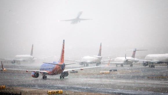 Planes line up on the tarmac as snow falls, delaying