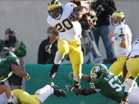 Michigan's Mike Hart (20) leaps between Michigan State's Eric Greg Jones, right, and Kaleb Thornhill, right, during the Wolverines' 28-24 win over MSU on Nov. 3, 2007 in East Lansing.