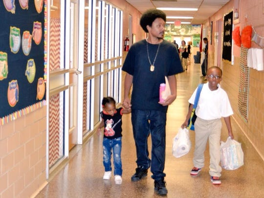 Gary Anderson (center) walks children Christopher Woods, 7, and Kamea Celestine, 3, down the third-grade hall at Cherokee Elementary to find Christopher's new classroom on Monday.