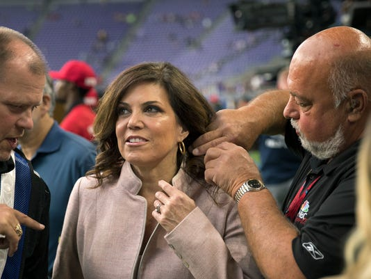 In an Aug. 28, 2017 photo, Michele Tafoya, sideline reporter for NBC Sunday Night Football, gets hooked up with a wireless mic by Technical manager Charlie Brown, right. Tafoya will be on the sideline reporting for NBC at her third Super Bowl, this time in Minnesota where her decorated career got a jump start more than 20 years ago. (Brian Peterson/Star Tribune via AP)/Star Tribune via AP)