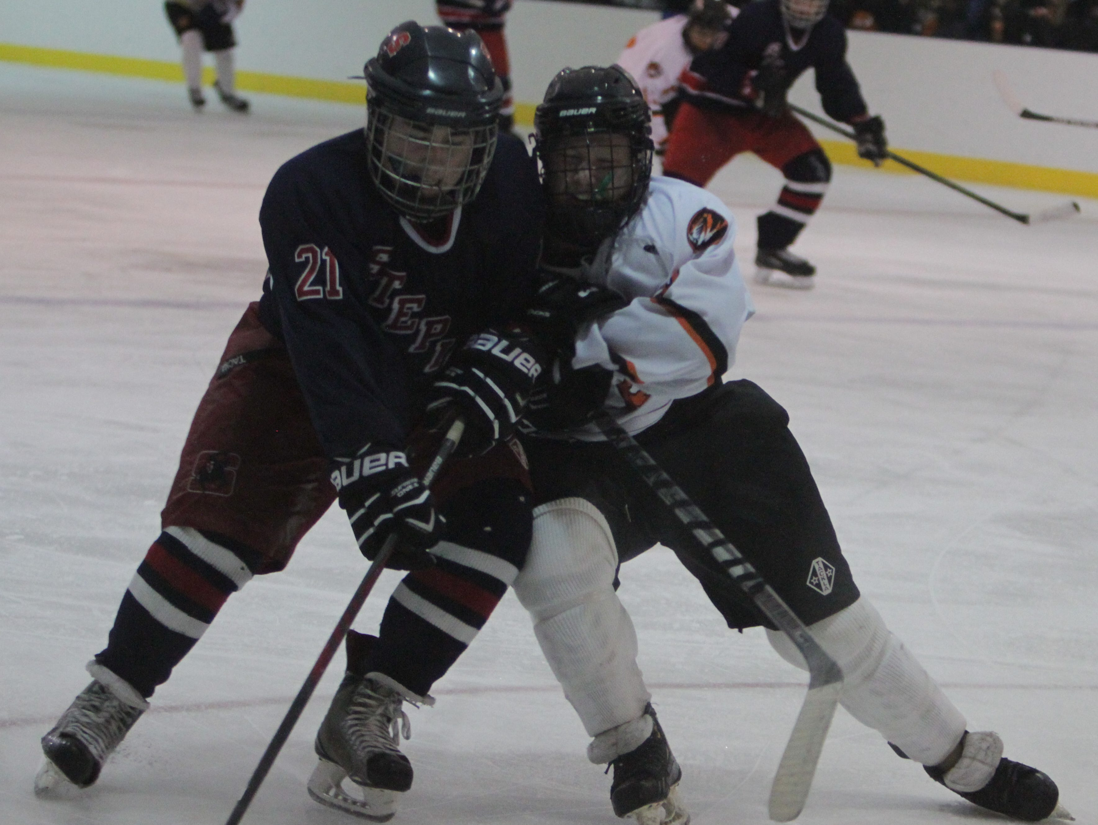 Stepinac's Brian Donovan (21) and White Plains' Liam Broderick battle for possession of the puck during the Guy Mathews Thanksgiving Invitational Hockey Tournament at the Ebersole Ice Rink on Saturday, November 28th, 2015. Stepinac won 7-3.
