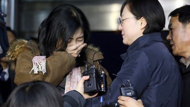 A Korean-American Shin Eun-mi, left, weeps  as she arrives to leave for the United Sates at the Incheon International Airport in Incheon, South Korea.