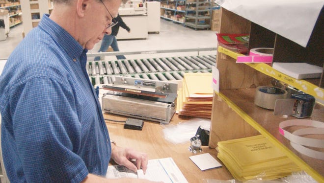 Seasonal employee Raphael Zepczyk does a final inspection on a Miles Kimball engraved lipstick holder before it is sent to the customer.
