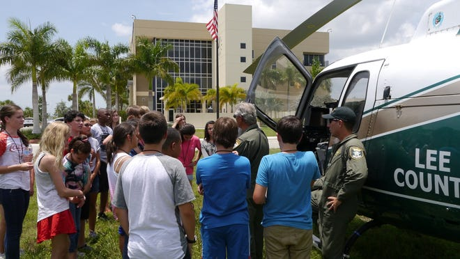 Kids watch as a Lee County Sheriff's Office chopper lands near the Cape Coral Police Department and pilots speak to them.