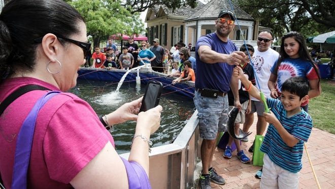 Virginia Guerra-Flores (left) takes a photograph of Daniel Flores, 6 (far right), during their first trip to the annual Earth Day-Bay Day on Saturday, April 9, 2016, at Heritage Park. Volunteer Israel Garcia (center), of the Kiwanis Club of Corpus Christi, helps Daniel display his fish.