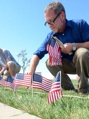 Frank Gonda helps to plant American flags outside of