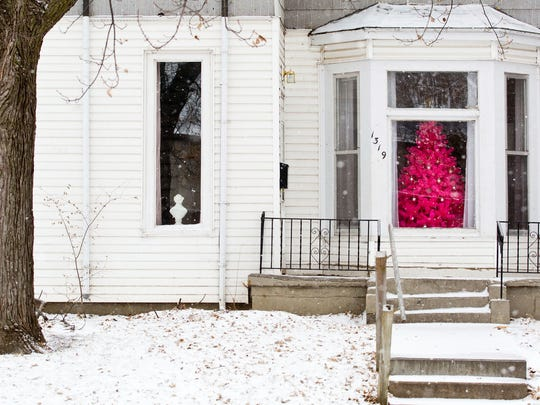 A hot pink Christmas tree is seen through a window as snow covers the yard of Luke and Megan Pettipoole's home near the Gerald R. Ford Birthsite, Saturday, Dec. 17, 2016, in Omaha. Ice and snow caused dozens of car crashes in Iowa and Nebraska, but it's the frigid temperatures coupled with strong winds that had officials warning residents Saturday to stay indoors.