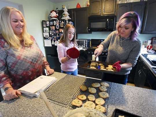 The chocolate chip cookies come out of the oven. From the left is Dena Haslup, Kammie Hollingshead and Magen Corbin.