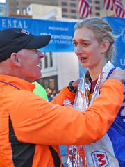 Nicole Michmerhuizen, center, is congratulated by elite runner coach Matt Ebersole, left, and Scott Morgan, right, after she crossed the finish line to become the women's winner of the Indianapolis Monumental Marathon, Saturday, November 7, 2015.