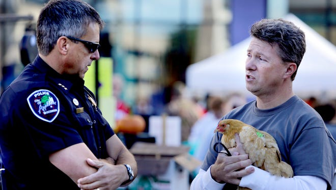 Open-carry protester Mark Scheffler of Appleton, Wis., holds a chicken as he talks with Appleton Police Deputy Chief Todd Olm on Sept. 21, 2013, at the Downtown Appleton Farm Market.