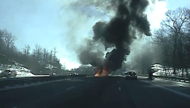 In this screen capture from a police dashcam video, a truck  is seen engulfed in flames on Rt. 15 south in Sparta on Thursday, Jan. 28, 2016, and narrowly missed hitting a police car and sergeant as it rolled backward unattended, striking a guardrail on the left shoulder, then coming to a stop.
