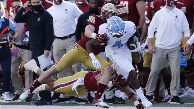 Boston College defensive back Mike Palmer (center left) stops North Carolina wide receiver Rontavius Groves (center right) during the first half of an NCAA college football game, Saturday, Oct. 3, 2020, in Boston. The Tar Heels defeated the Eagles, 26-22.