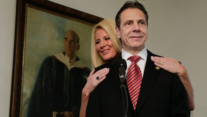 New York Gov. Andrew Cuomo speaks to members of the media as his partner, Sandra Lee, looks on after casting his ballot in Mount Kisco, N.Y. on Nov. 4, 2014.