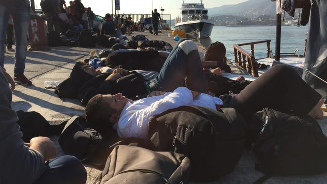 Migrants sleep on a dock on the island of Lesbos, in Greece, on Sept. 19.