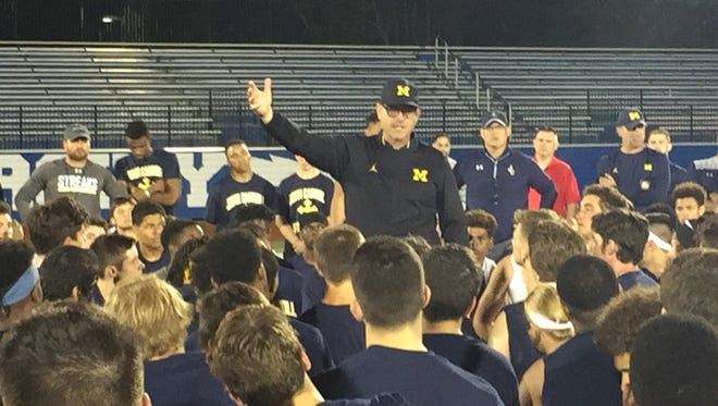 Michigan coach Jim Harbaugh addresses players at the end of the satellite camp Friday in University Heights, Ohio.