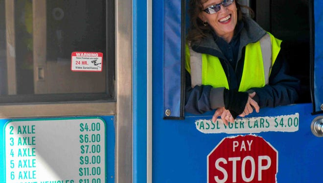 Deborah Cooper, of Elkton, Md., collects tolls from motorists at the Newark Toll Plaza.