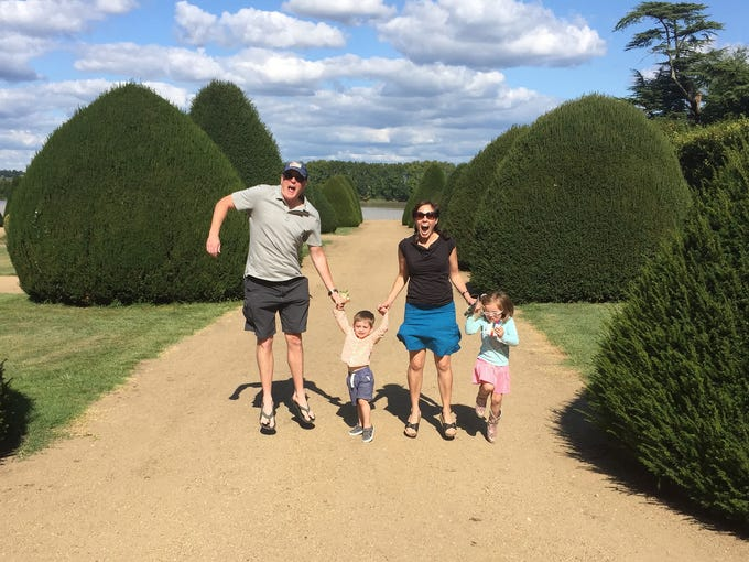 The Hughey family jumps for joy in the gardens of Chateau