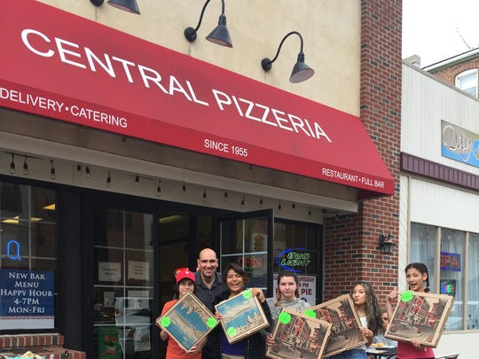 Students show off their pizza boxes marked for the sticker shock program at Central Pizzeria in Somerville.