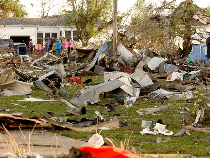 Quapaw, Okla.,  residents survey the damage in a residential neighborhood struck by a tornado on Sunday evening, April 27, 2014. A powerful storm system rumbled through the central and southern United States on Sunday, spawning a massive tornado that carved path of destruction through the northern Little Rock suburbs and another twister that killed two people in Oklahoma and injured others in Kansas. (AP Photo/Tulsa World,  Gary Crow)