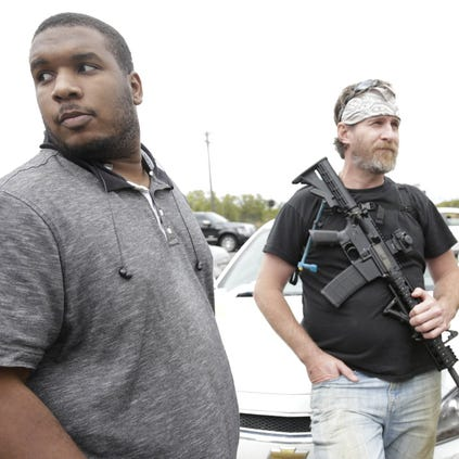 Elijah Woody, 24, of Detroit, left, waits on fellow protestors to show their support of him after his  arrest last week. Hells Saint's, an organization that supports open-carry laws, protest Sunday Sep. 21, 2014 in Detroit  of the recent arrest of Woody.
