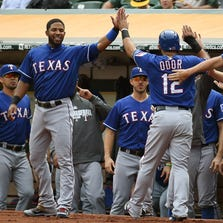 OAKLAND, CA - SEPTEMBER 18:  Rougned Odor #12 of the Texas Rangers is congratulated by Elvis Andrus #1 (L) and hitting coach Dave Magaden #14 (R) after Odor scored against the Oakland Athletics in the top of the first inning at O.co Coliseum on September 18, 2014 in Oakland, California.  (Photo by Thearon W. Henderson/Getty Images)