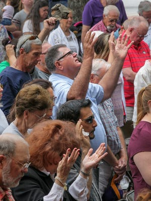Larry Erskine, middle, raises his arms with others, as Elva Martin, coordinator of the Internet Prayer Task Force, prays during the National Day of Prayer on the Anderson County Courthouse Plaza at noon on Thursday.