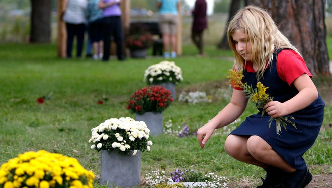 London Rabec, 9, places wildflowers on the burial row markers after the Outagamie County Cemetery memorial dedication Thursday, Sept. 24, in Grand Chute.
