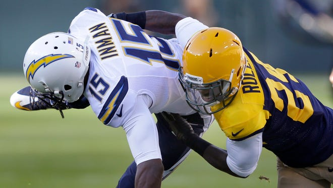 Green Bay Packers cornerback Quinten Rollins  tackles San Diego Chargers wide receiver Dontrelle Inman following a pass reception.The Green Bay Packers host the San Diego Chargers, Sunday, October 18, 2015 at Lambeau Field in Green Bay, Wis.