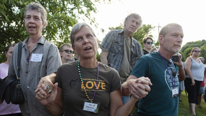 Cathy Thompson and Theresa and Tom Hannah sing at the conclusion of a rededication of the Fox Valley Unitarian Universalist Fellowship's Black Lives Matter banner in July. The sign has now been stolen for the fourth time.