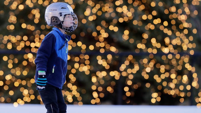 Ben Renkas, 6, of De Pere, skates past the Christmas tree on the ice skating pond Thursday in Titletown. The park is part of the Green Bay Packers' Titletown District in Ashwaubenon.