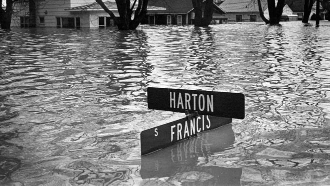 A photo from Lansing's April 1975 flood. A street sign barely survives as the Red Cedar river takes over the first floor of homes on the east side of Lansing, near the east end of I-496. Photo taken April 21, 1975.