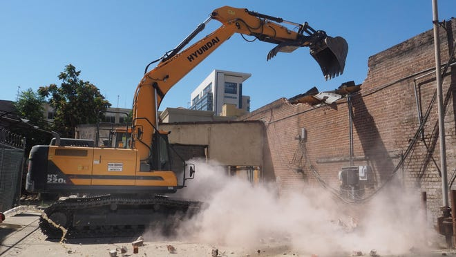 Rob Moore of R B Environmental operates the excavator as it tears down a brick wall on the former J.F. Donaldson Tires building located on Hunter Street next to the Avenue Inn.