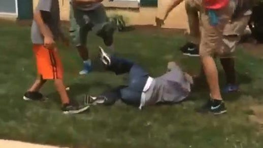 Screen grab from the video of teens attacking a mentally-challenged man.
