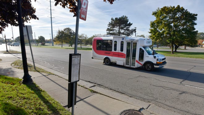 A SMART connector bus drives past the Beaumont Botsford Hospital Grand River stop.