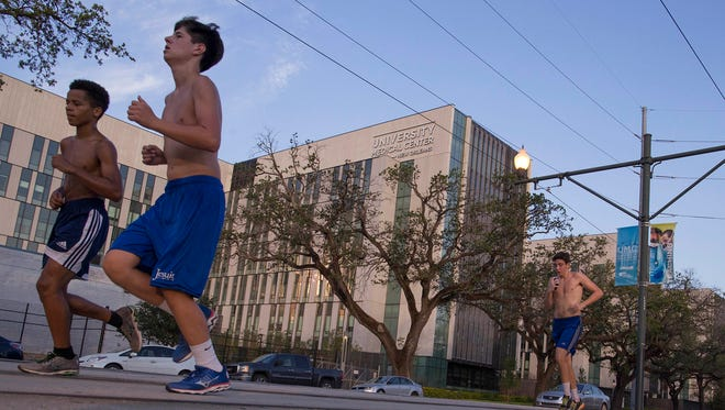 Students from Jesuit High School of New Orleans run past the newly opened $1.1 billion University Medical Center on Saturday, Aug. 15, 2015, which was built to replace Charity Hospital, which flooded during Hurricane Katrina.
