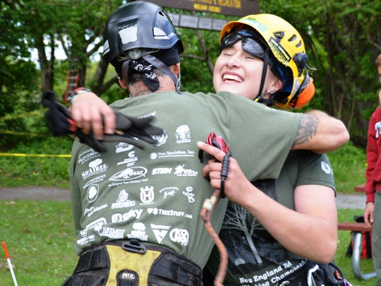 Rachel Brudzinski of New York City hugs her competitors after a good climb at the New England Tree Climbing Championship at Oakledge Park in Burlington on Saturday.