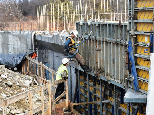 Vermont civil engineers gave the state's bridges a 'C' grade, but noted the state has made significant progress addressing the maintenance backlog. Here is one project. Karl Larson of Bristol removes forms from concrete on the new Route 116 bridge over the New Haven River in Bristol on April 8.