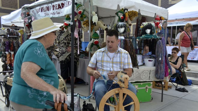 Barb Ferguson, left, of North Fond du Lac talks with Josh Steger as the fiber artist from De Pere spins yarn with a spinning wheel at Artstreet on Sunday, Aug. 28, 2016. Steger owns the Icon Fiber Arts studio in Ledgeview and is a member of the local Traveling Treadlers Fiber Arts Guild.
