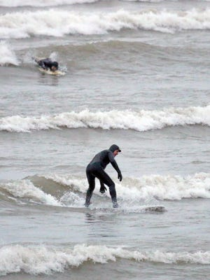 Surfers take to the waves Jan. 10, 2017, in Lake Michigan on the shores of Sheboygan, Wis., despite near-freezing temperatures at the lakefront.