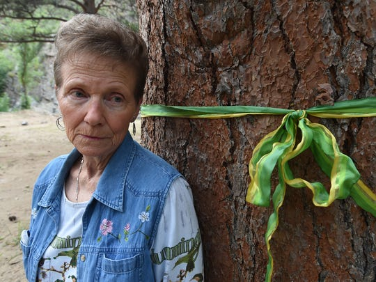 Barb Anderson stands next to the tree that neighbor, Mike Horn, had clung to during the food last in the Big Thompson Canyon on Aug. 27. She tied a ribbon around the tree as a reminder of the day that Horn saved himself from being washed away from the rushing river.